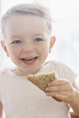 Portrait of a smiling young boy eating a sandwich.