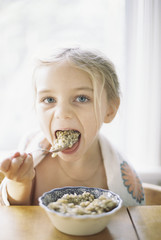 Young girl sitting at a table, eating breakfast from a bowl.