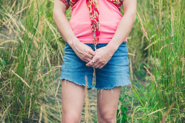 Young woman standing in tall grass