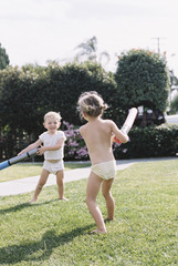 Young girl and young boy, two children wearing T-Shirt and shorts playing in a garden.