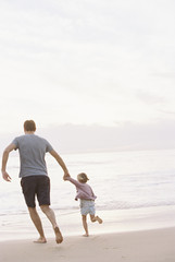 Man playing on a sandy beach by the ocean, holding his young daughter's hand.