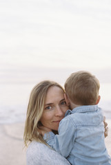 Woman standing on a sandy beach by the ocean, holding her young son in her arms.