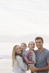 Couple standing with their son and daughter on a sandy beach by the ocean, looking at camera, smiling.