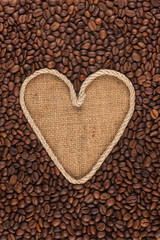 Symbolic heart made of rope lies on sackcloth and coffee beans