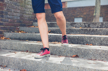 Legs of young woman walking down steps