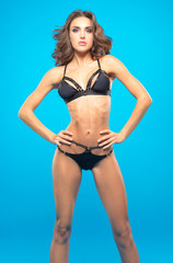 Athletic girl in a bathing suit on a blue background