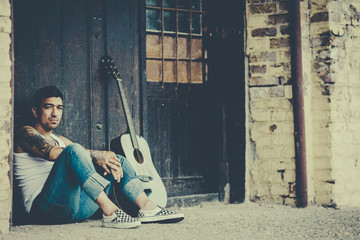 Hipster male with tattoes with guitar