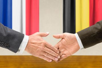Vertreter Frankreichs und Belgiens reichen sich die Hand