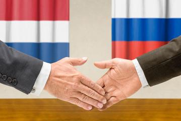 Vertreter der Niederlande und Russlands reichen sich die Hand