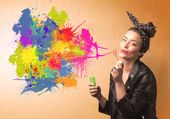 Cute girl blowing colorful splash graffiti