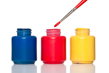 Colorful paint containers and a brush