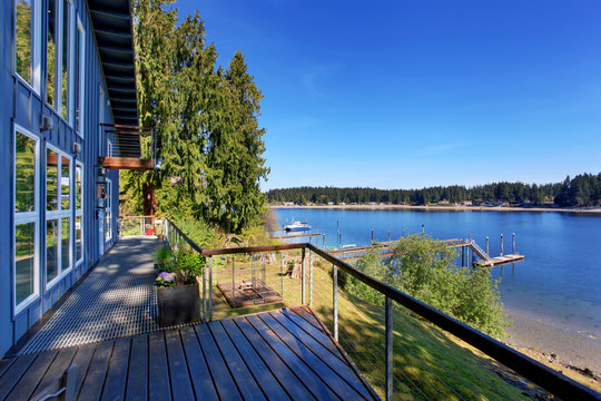 Large covered porch of luxury home with lake view.