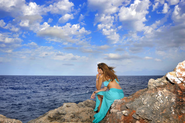 woman looking at sea horizon thoughtful from rock cliff  in relax concept