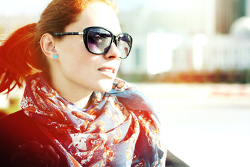 Portrait of an attractive young woman in sunglasses outdoors