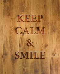 """Text """"Keep Calm & Smile"""" engraved in wooden background"""