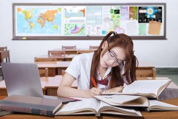 Brunette student doing her task in the class