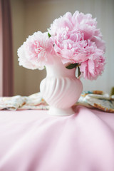 Pink Peonies in a ceramic vase in natural light.