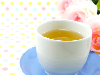 tea in cup on sweet polka dot background