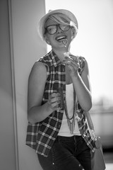 portrait of laughing hipster girl blowing soap bubbles on street