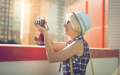 portrait of smiling hipster girl making photo on film camera