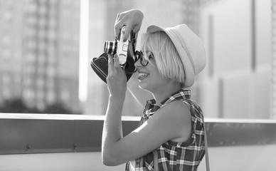Black and white portrait of hipster girl using retro film camera