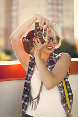 portrait of young blonde girl making picture on retro camera