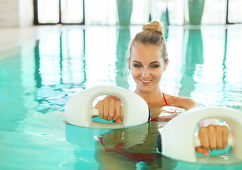 Blond woman doing aqua aerobics with foam dumbbells in swimming