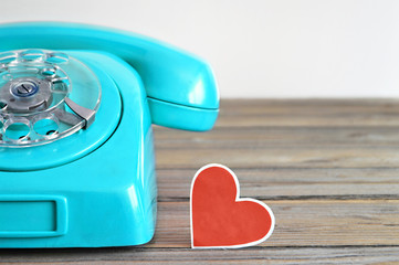 Old blue telephone and heart  shaped tag on wooden background