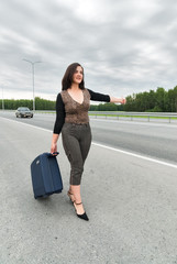 Beautiful woman with suitcase stopping cars