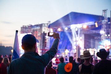 young man taking pictures rock concert on phone