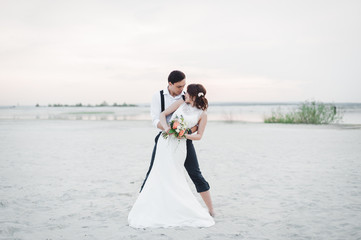Bride and groom dancing barefoot on the sand