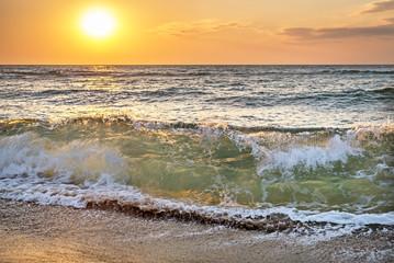 Beautiful sunrise at the sea with shorebreak splashes on sandy b