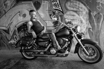 Tough guy leaning back on a chopper bike in front of a graffiti