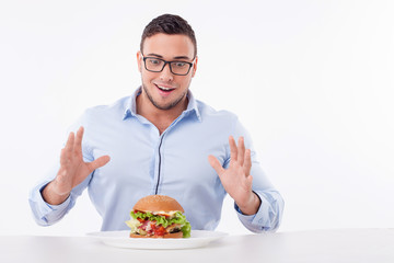 Cheerful young fit man is very hungry