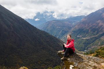 Wall Mural - Young woman tourist sitting mountain edge rock. Nepal.