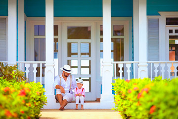 cute father and son sitting on porch, caribbean exterior