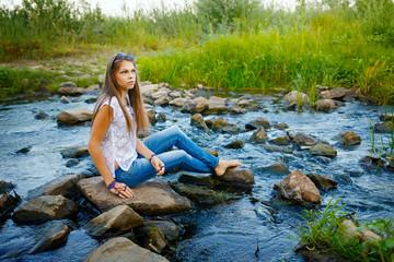 Boho Girl sitting on rocks in river.