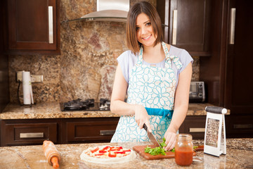Pretty girl making a pizza and smiling