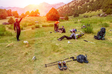 Hikers break on grassy lawn. 