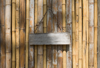 Wooden signboard on bamboo background