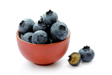 Blueberries in a clay bowl, whole and sliced fruits isolated on