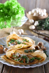 Pancakes with creamy mushrooms on wooden background