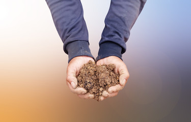 Hand holding soil,Hand dirty with soil on abstract blurred background.