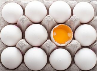 A dozen of eggs in carton showing yolk