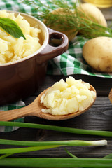 Mashed potatoes in bowl on wooden table with checkered napkin, closeup
