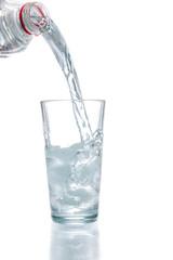 Trinkwasser aus einer Flasche in ein Glas mit Eiswürfeln gieße