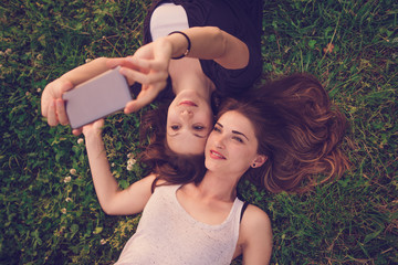 Two young woman lying on the grass and taking selfie with mobile phone