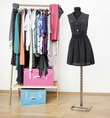 Dressing closet with polka dots clothes arranged on hangers and an outfit on a mannequin. Colorful wardrobe with polka dots clothes and accessories.