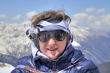 Dombay. Woman in glasses from the sun on a background of mountai