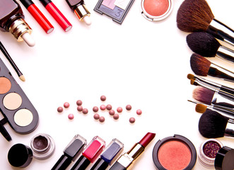 Set of professional cosmetic: make-up brushes, shadows, lipstick, nail polishes - partly isolated with shadows on white background. Overhead view. Front part. Place for your text.